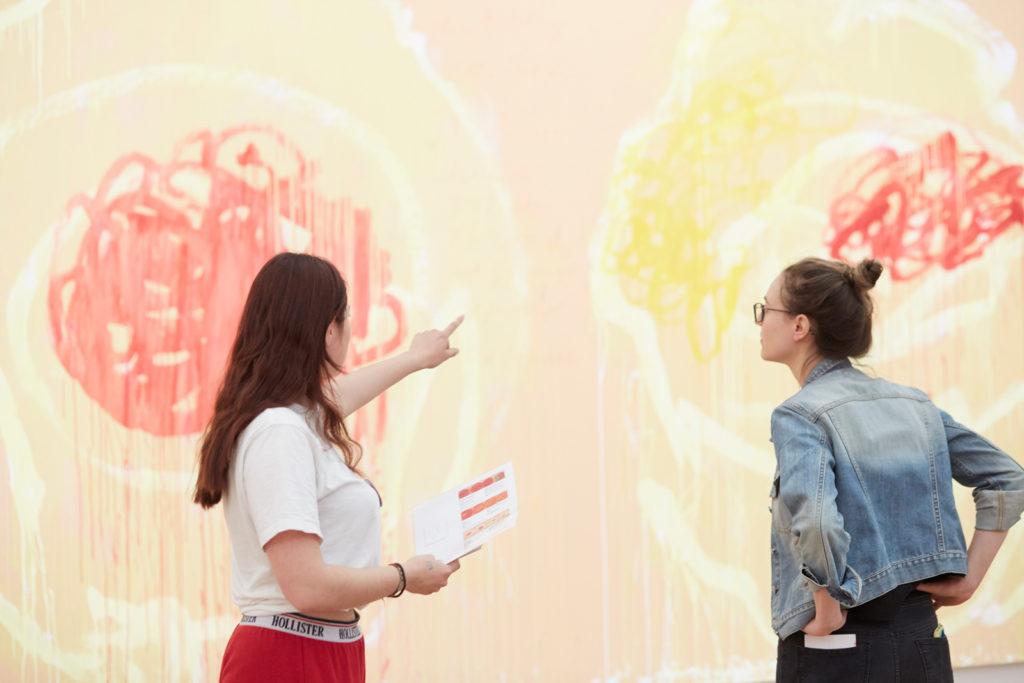 Zwei Schülerinnen besprechen ein Kunstwerk