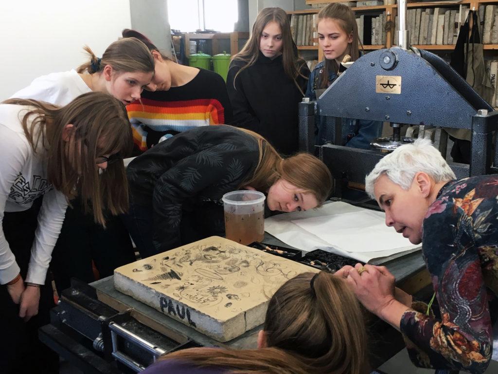 Schülergruppe beim Kennenlernen einer Druckerpresse