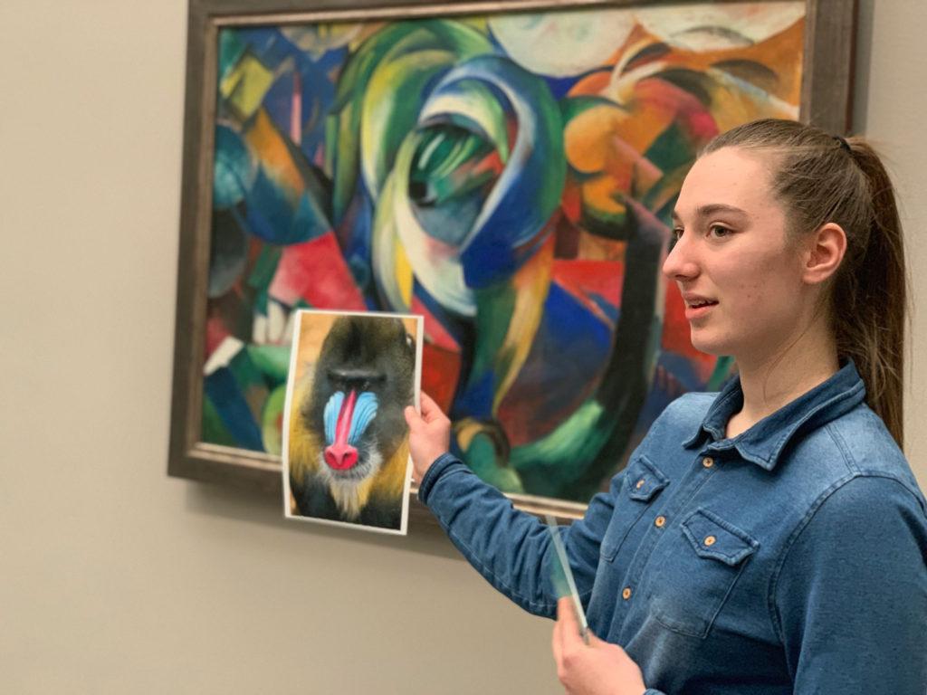 Schülerin erklärt die Farbgestaltung eines Gemäldes